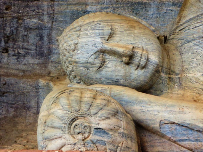 Stone image carving of Buddha up close, lying on a bolster
