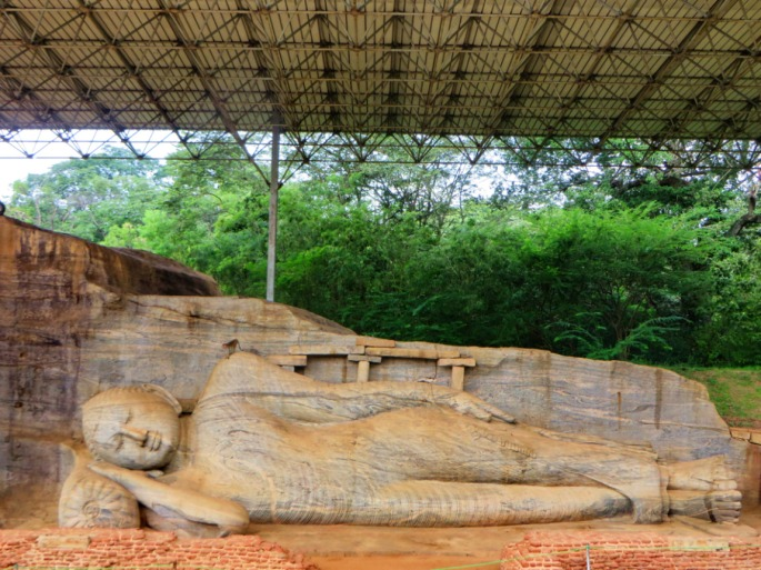 stone carving of Buddha lying down, depicting his parinirvana