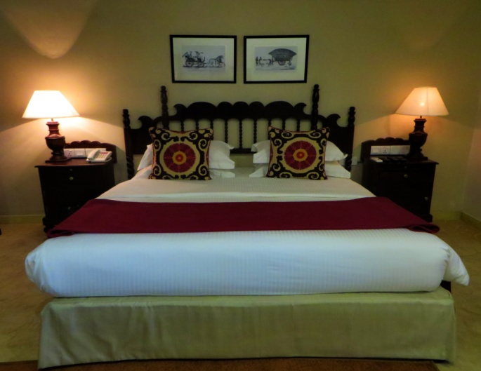 king sized bed, two bedside desks and lamps, and paintings inside the superior room of Ekho Lake House