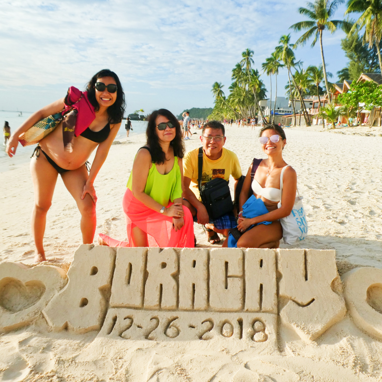 family photo on the beach with Boracay sand sculpture