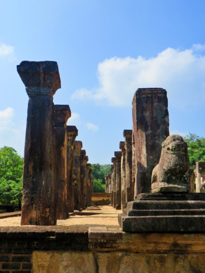 stone pillars of the council chamber of King Nissankamalla and a stone statue of a lion guardian in Polonnaruwa