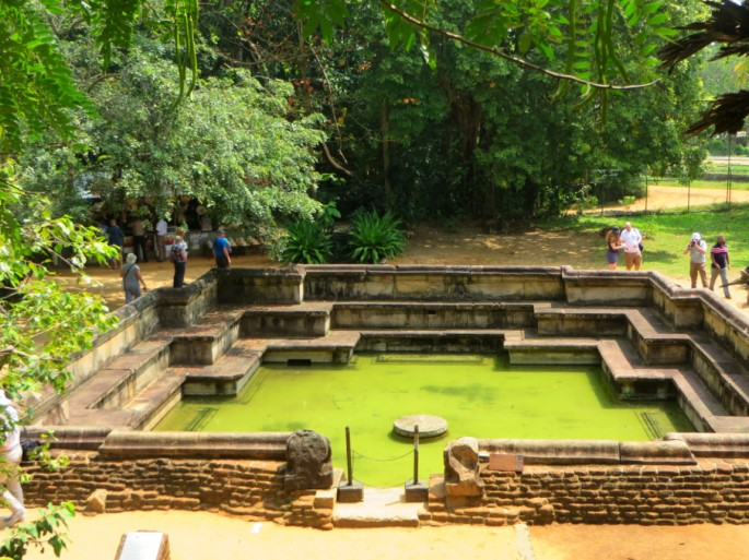 tourists walk along the sides of the kumara pokuna, an ancient royal bath in the city of Polonnaruwa
