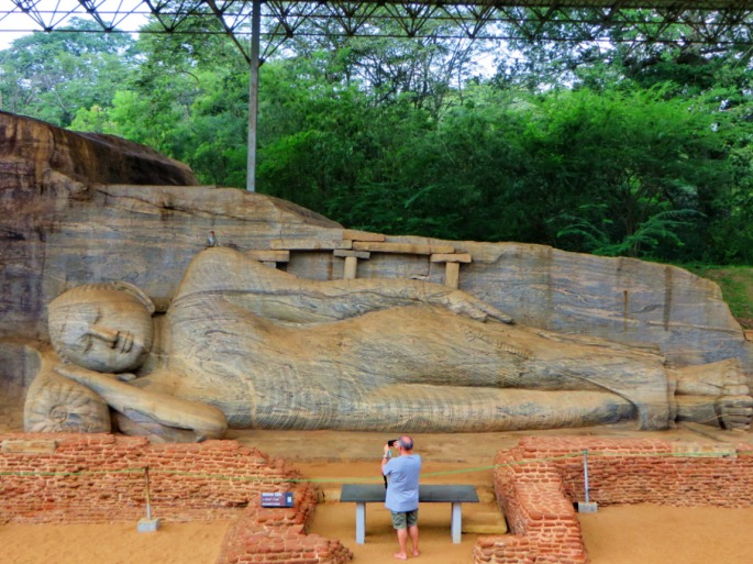 tourist taking a photo of the reclining Buddha is dwarfed by the stone statue