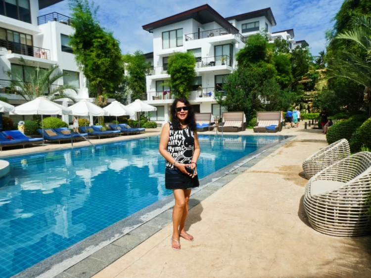 woman stands by the pool with the hotel as backdrop