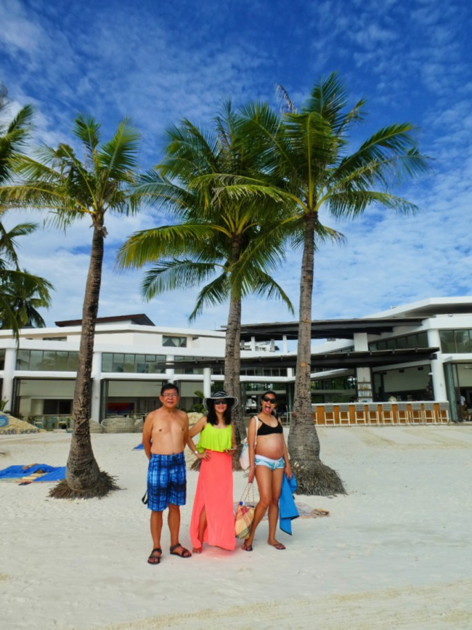 family photo on the beach in front of palm trees and the hotel exterior
