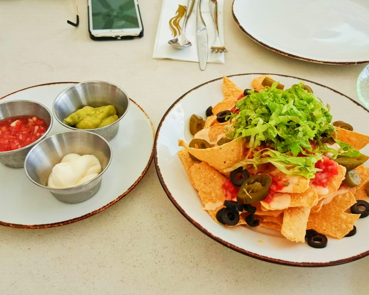 nachos plate with salsa, guacamole, and sour cream