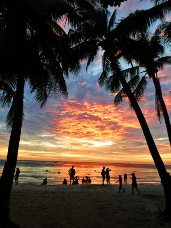 skies illuminate like fire as the sun sets on the island
