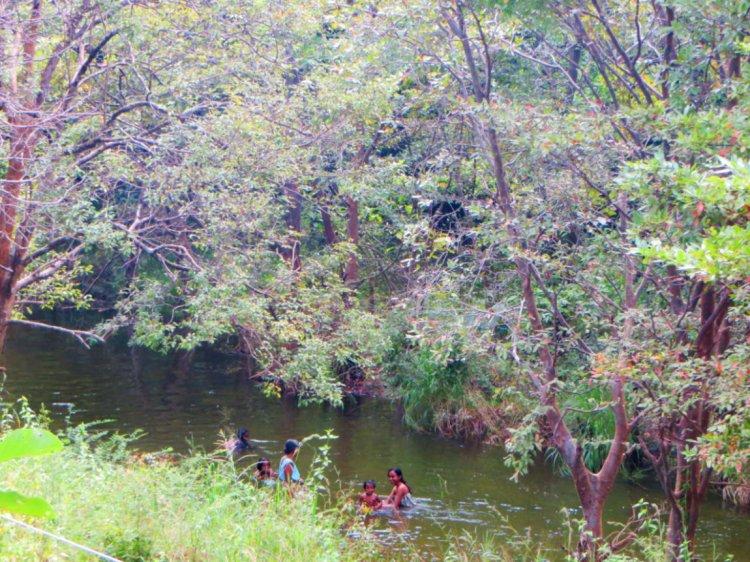local Sri Lankans take a bath in the river heading towards Minneriya Park