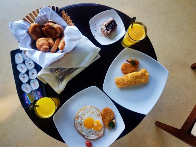Eggs, orange juice, a bread basket, and jams for breakfast